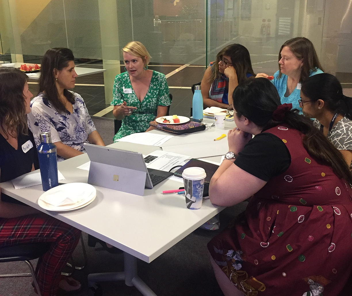 Photo of Zel Iscel in discussion with team about policies and procedures for accessibility in the workplace.