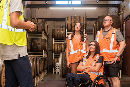 woamin in wheelchair with colleagues receiving some training working in winery with wine barrels