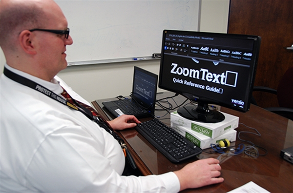 man typing on keyboard with a computer screen displaying large text