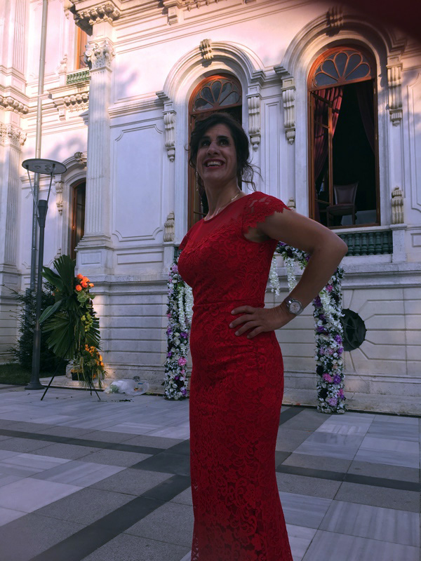 Zel the owner of Inclusive World in a beautiful red lace dress in front of an historic looking white building.